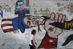 A woman walks past graffiti in Caracas
