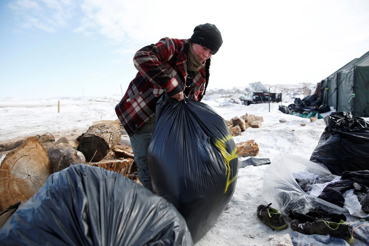 Crystal Houser bags excess blankets for delivery to nearby communities while helping to clean up the opposition camp against the Dakota Access oil pipeline near Cannon Ball